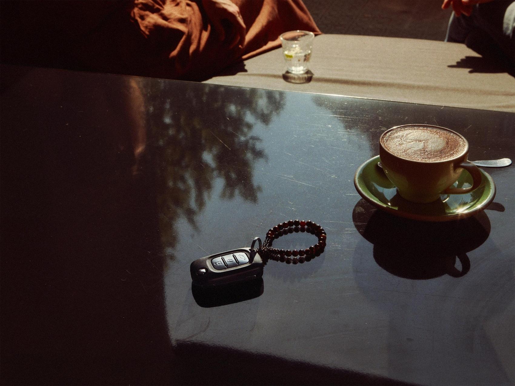 La clé de voiture se trouve sur une table à côté d'une tasse de café.