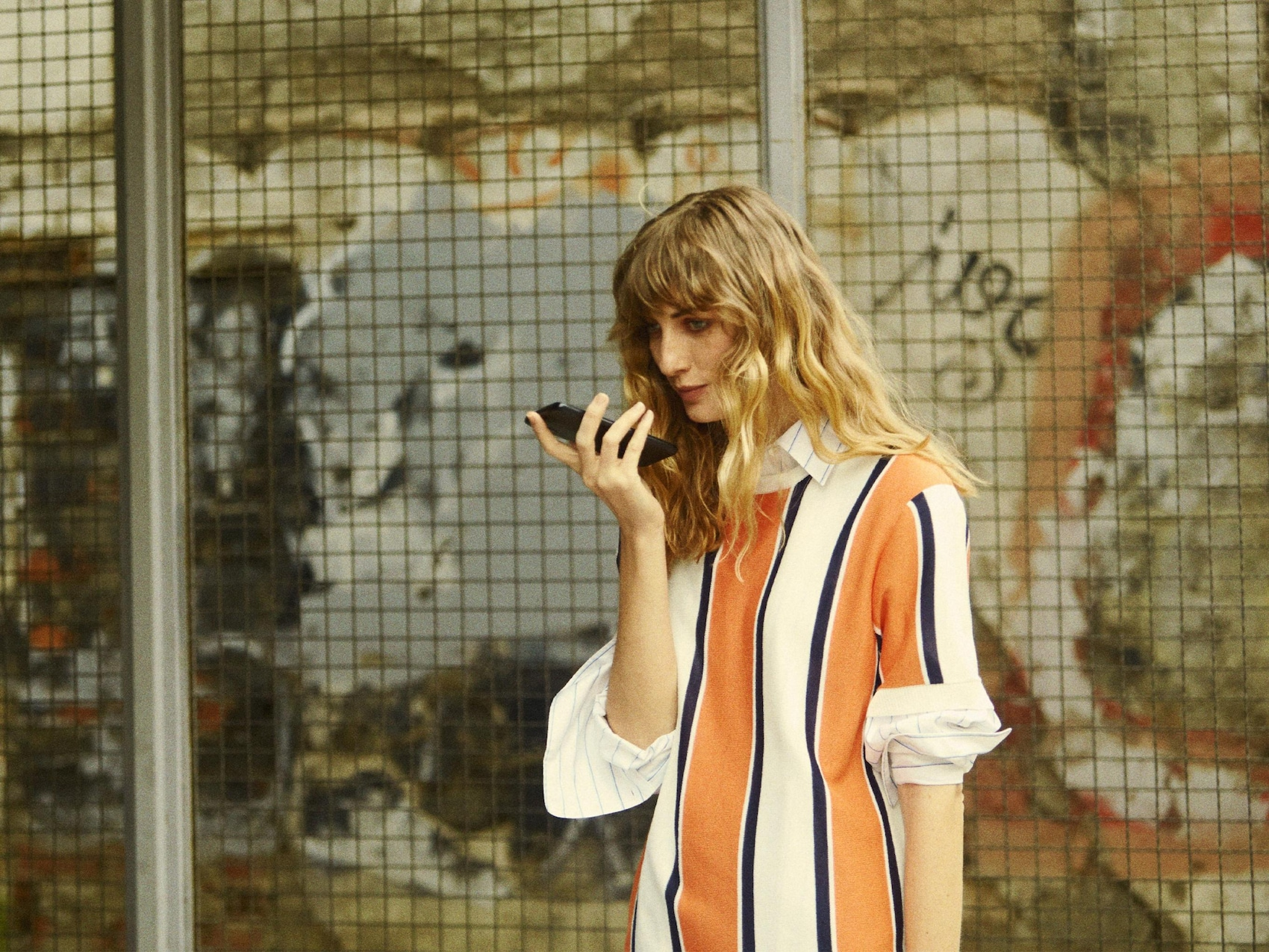Eine junge Frau mit Smartphone vor einem Gitter.