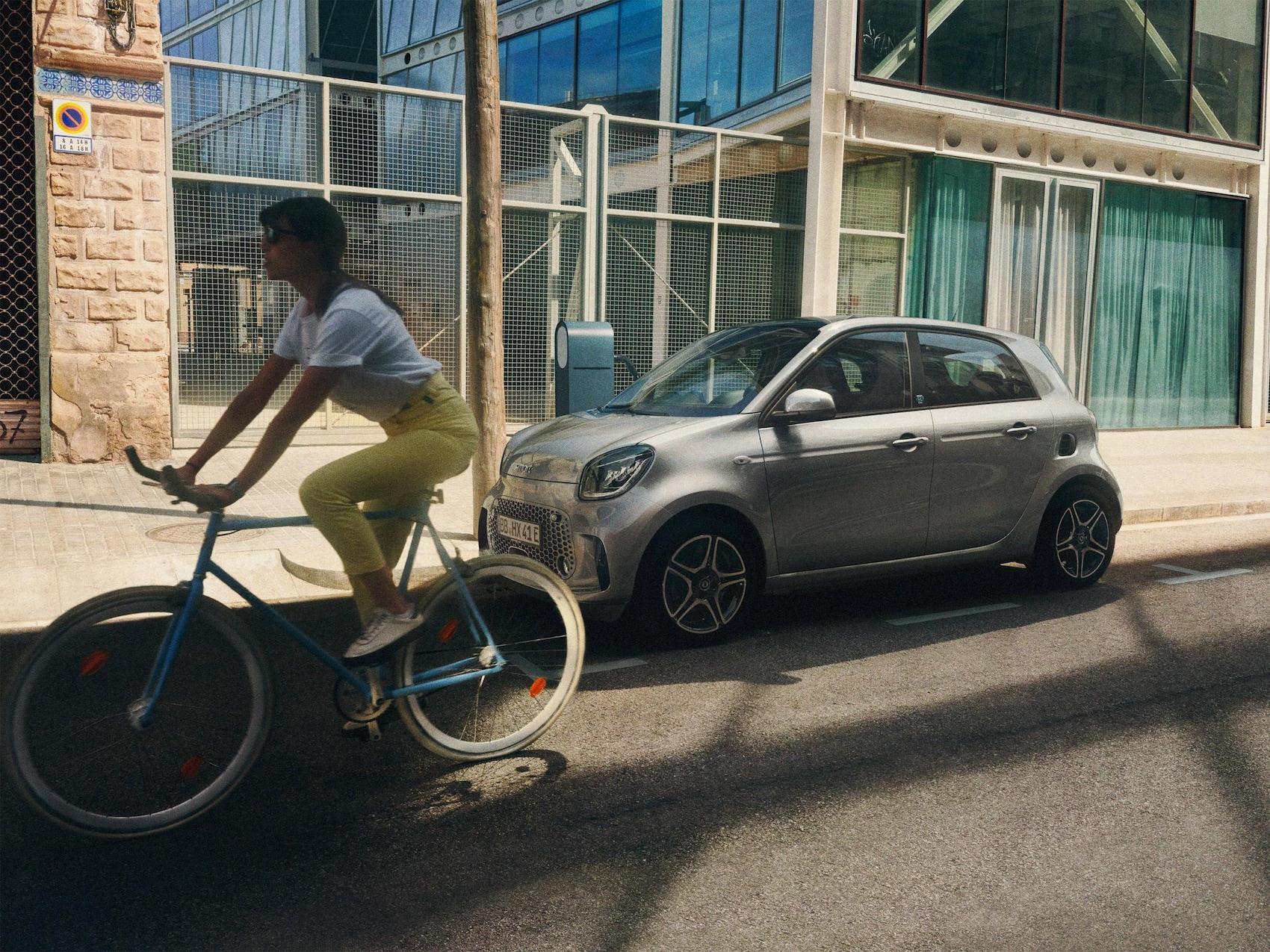 Une smart EQ forfour stationnée le long du trottoir. Un cycliste passe à côté.