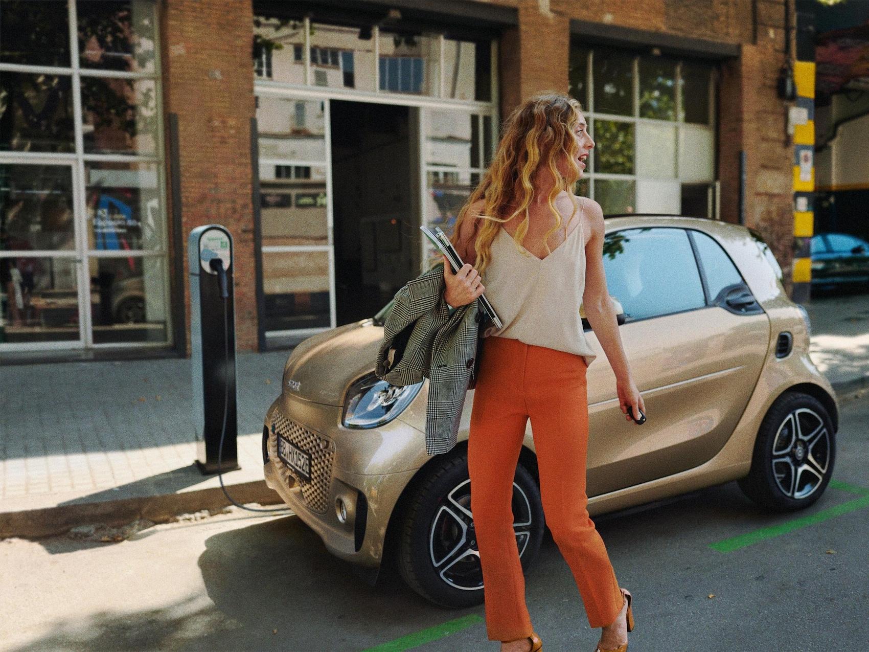 Une smart EQ fortwo garée au niveau d'une borne de recharge derrière une jeune femme.