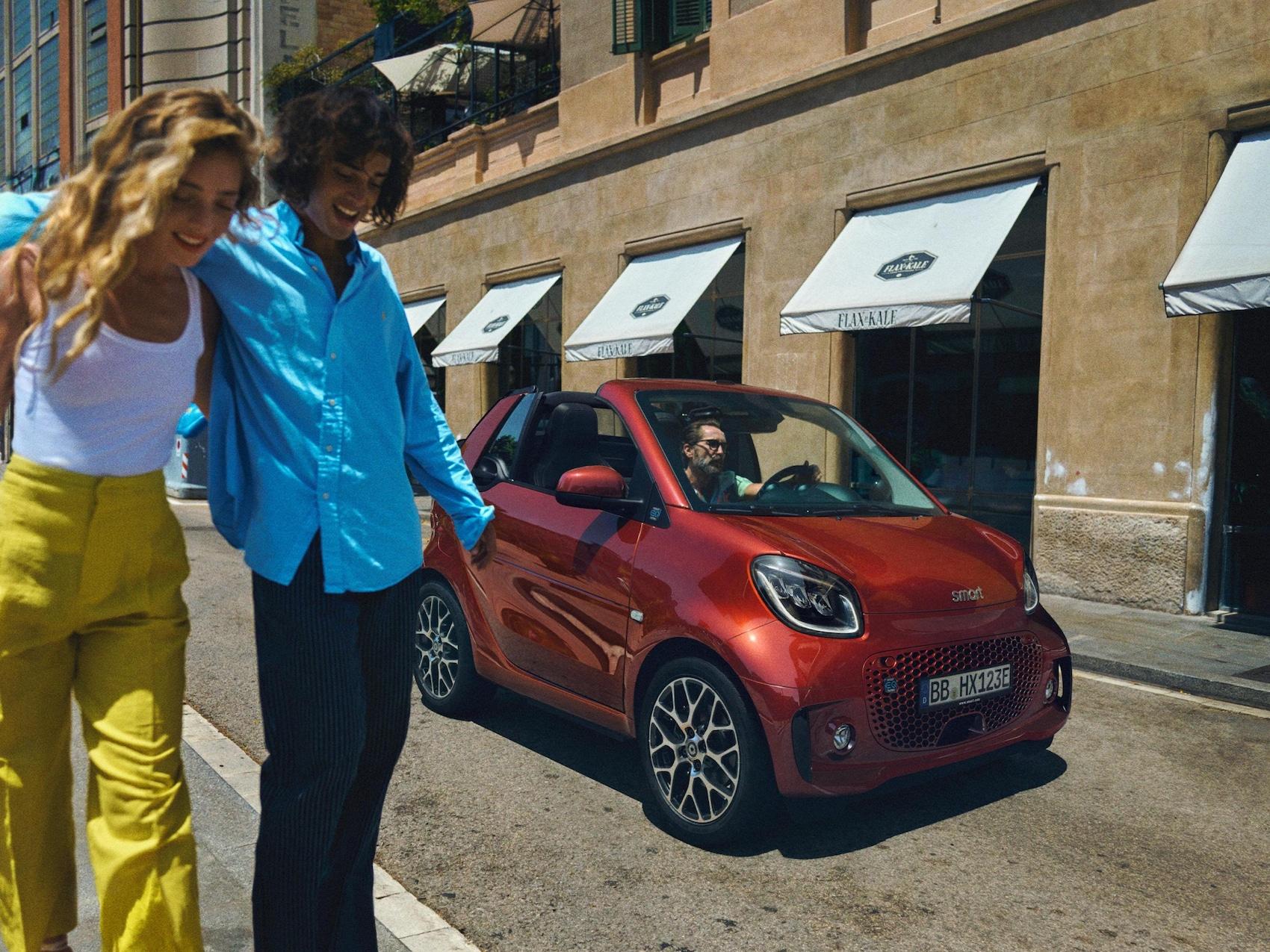 Une homme et une femme entrelacés passent devant une smart EQ fortwo cabrio.