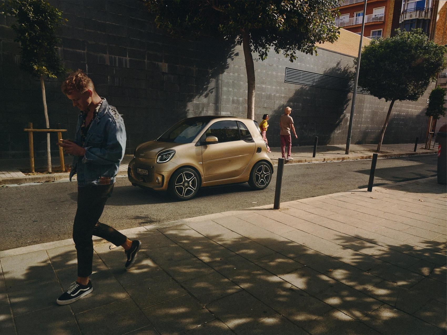 Ein smart EQ fortwo auf der Straße mit Fußgängern.