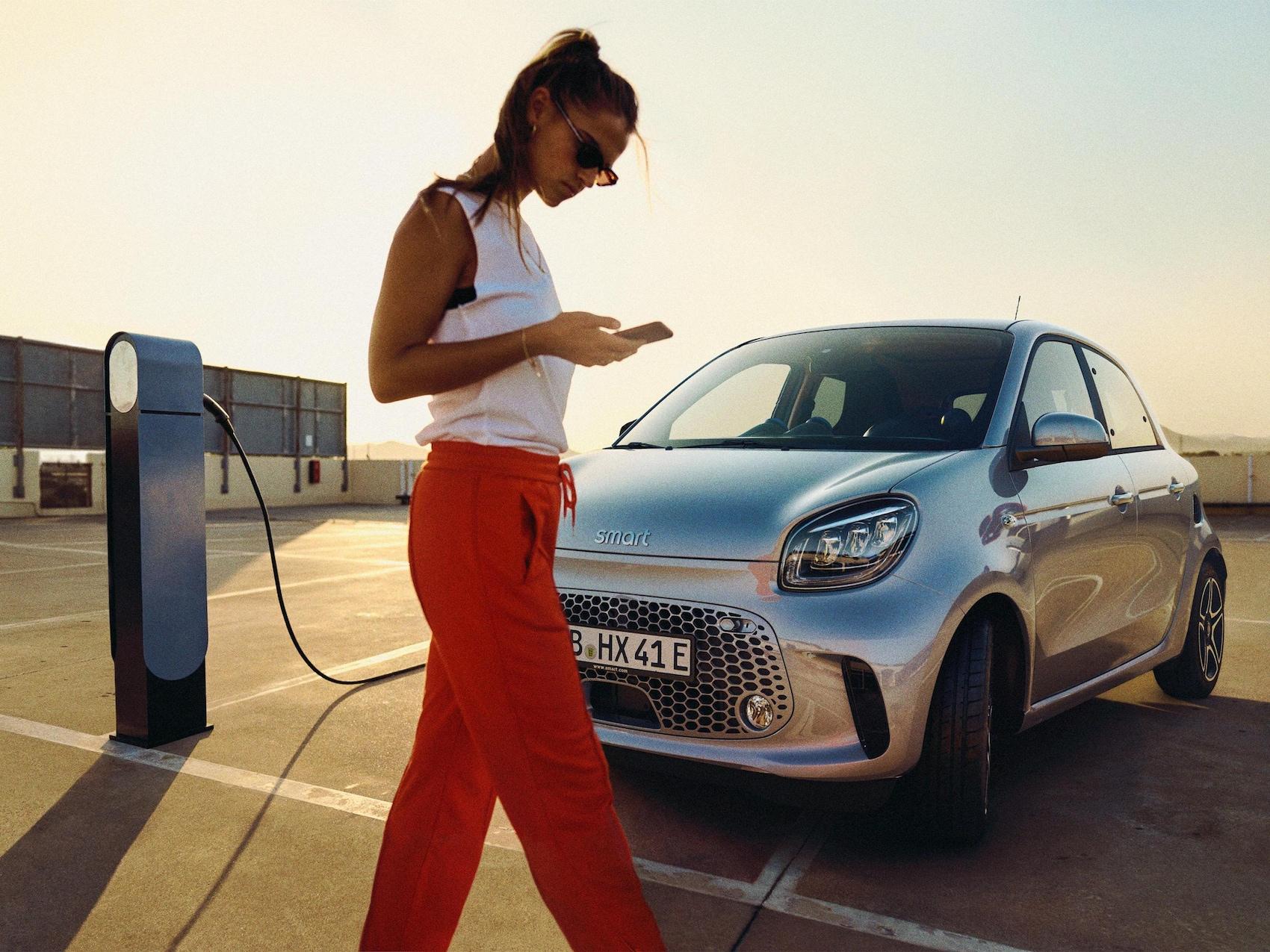 Uma mulher encontra-se em pé ao lado de um smart EQ fortwo em carregamento num parque de estacionamento solarengo.