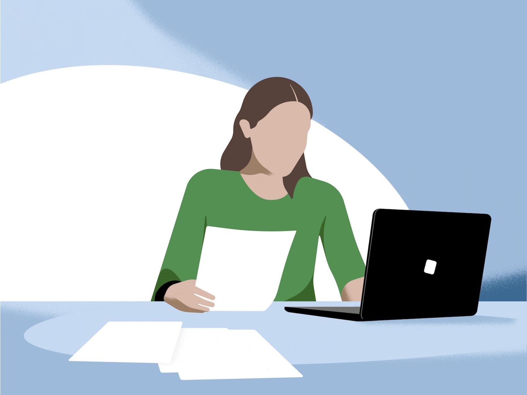 Nainen istuu avatun kannettavan tietokoneen ääressä.