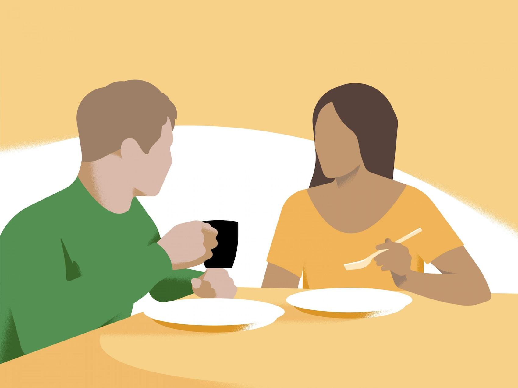 Dve osebi sedita za mizo in jesta.