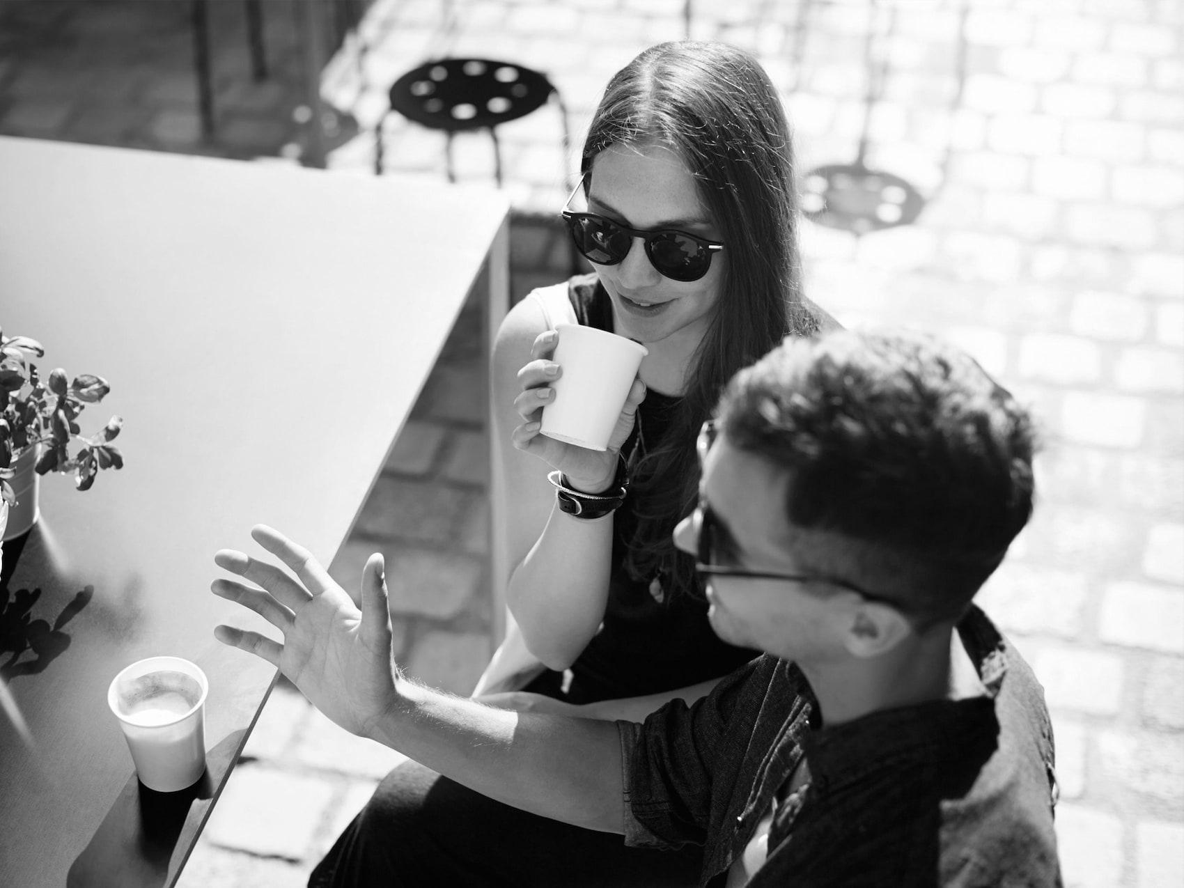 Una ragazza e un ragazzo si ricaricano bevendo un caffè al tavolo.