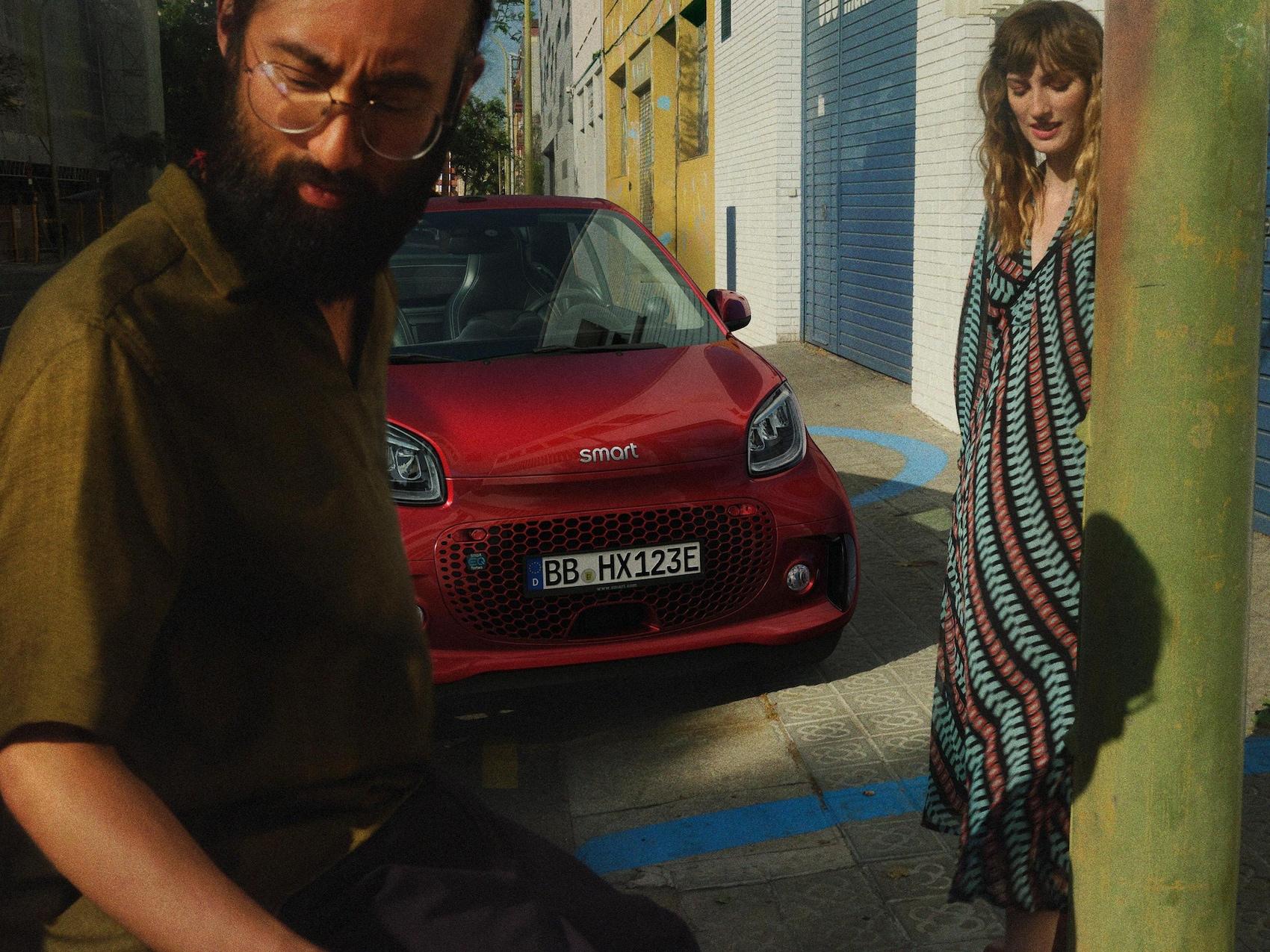 Un homme et une femme se tiennent devant la smart EQ fortwo cabrio