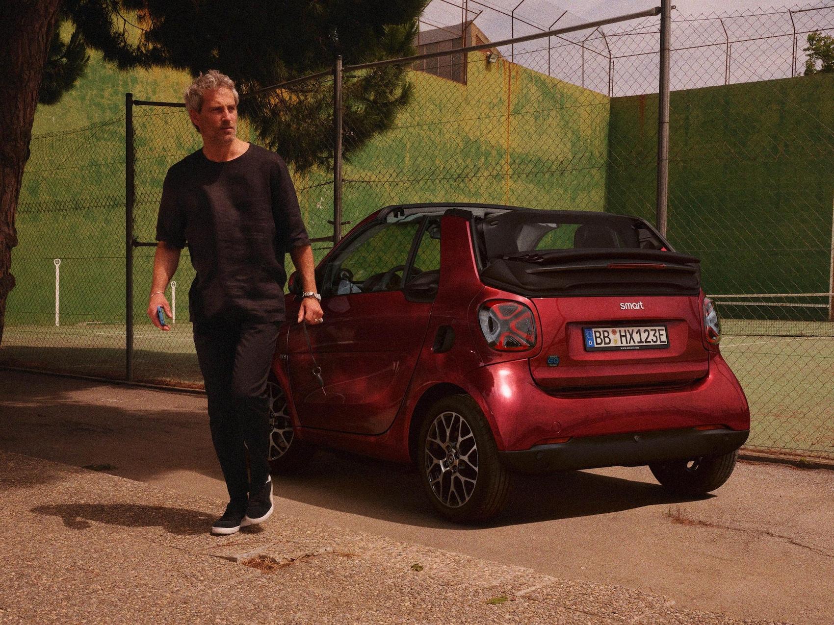 Un homme se tient devant une smart EQ fortwo cabrio