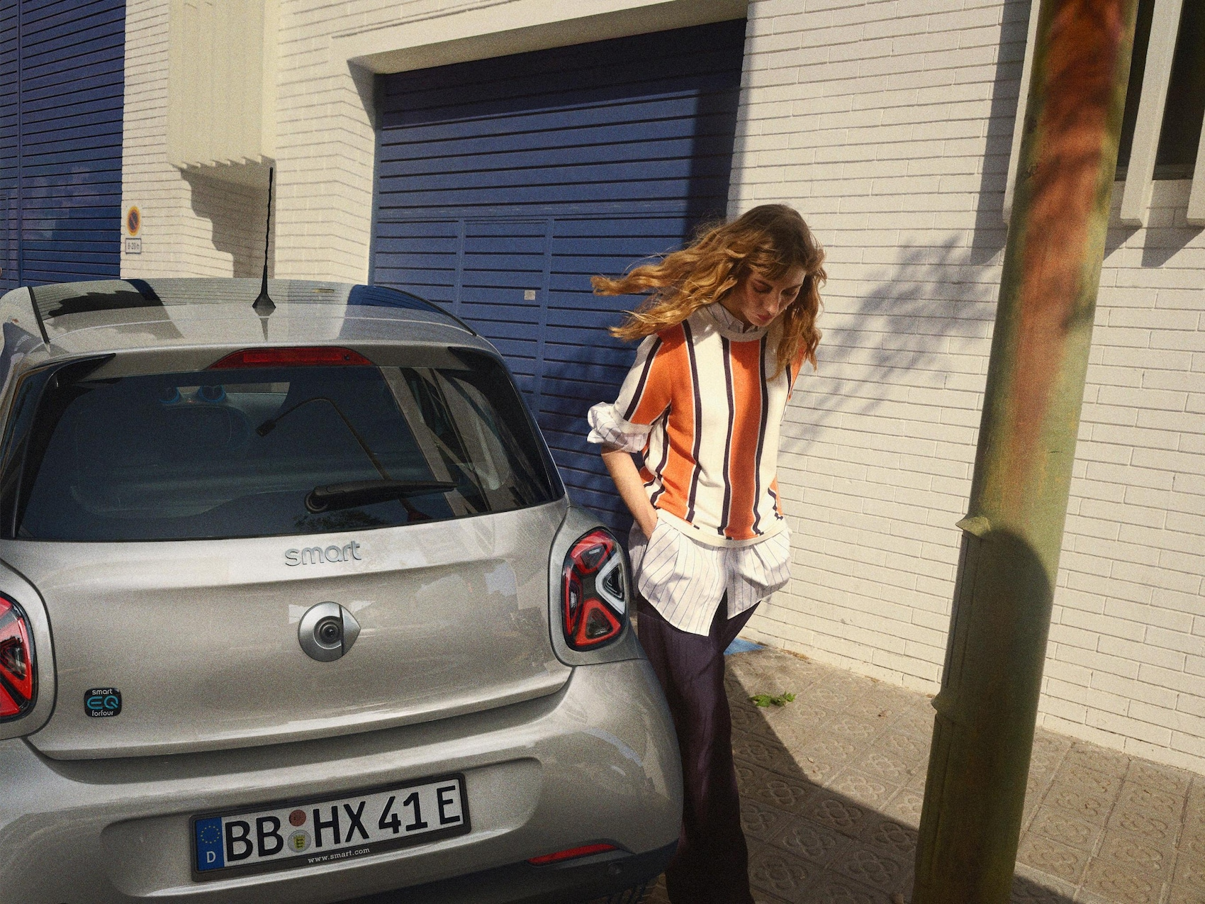 Dve ženy prechádzajú okolo vozidla smart EQ forfour