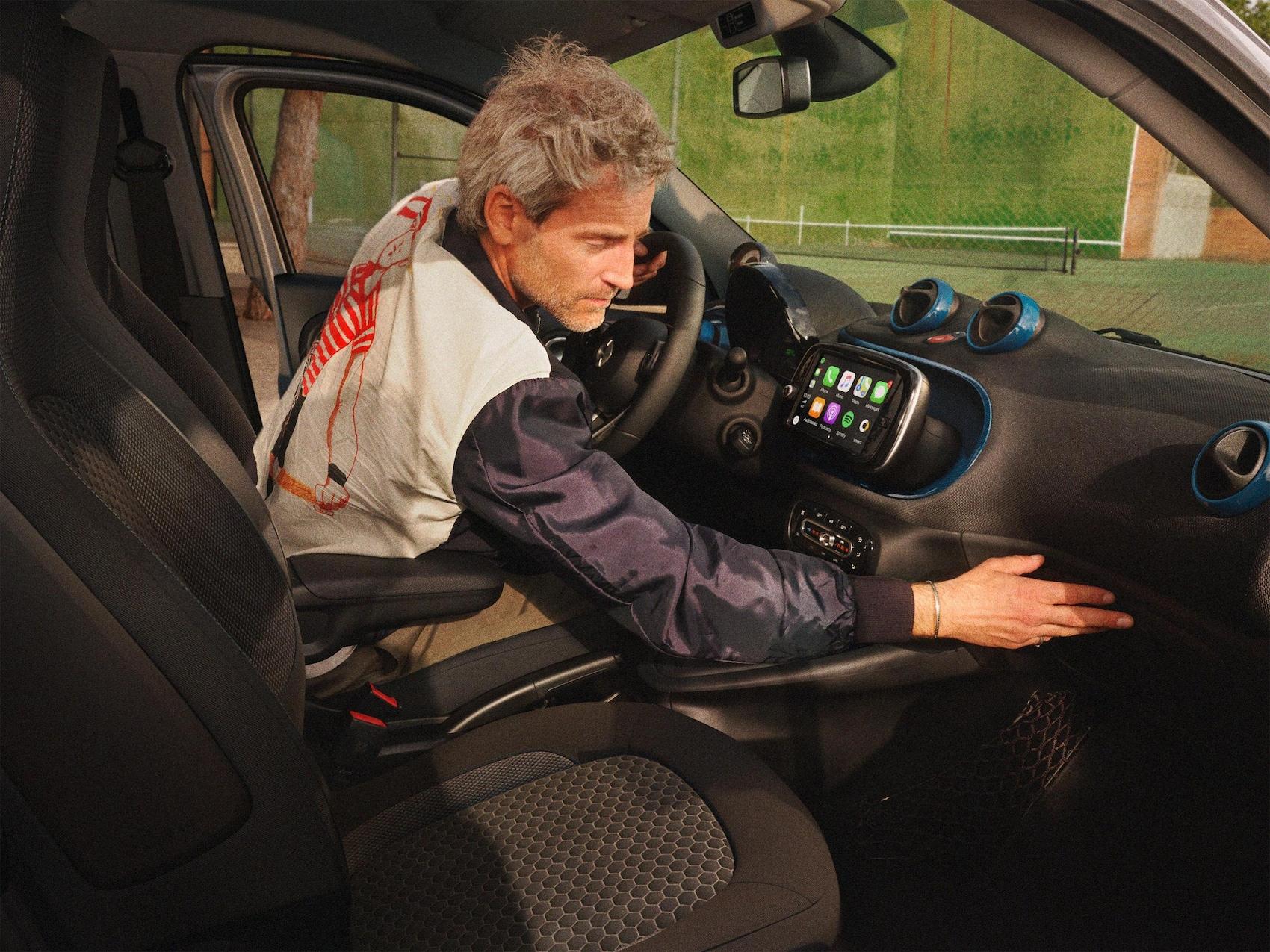Muž sedí za volantom vozidla smart EQ forfour