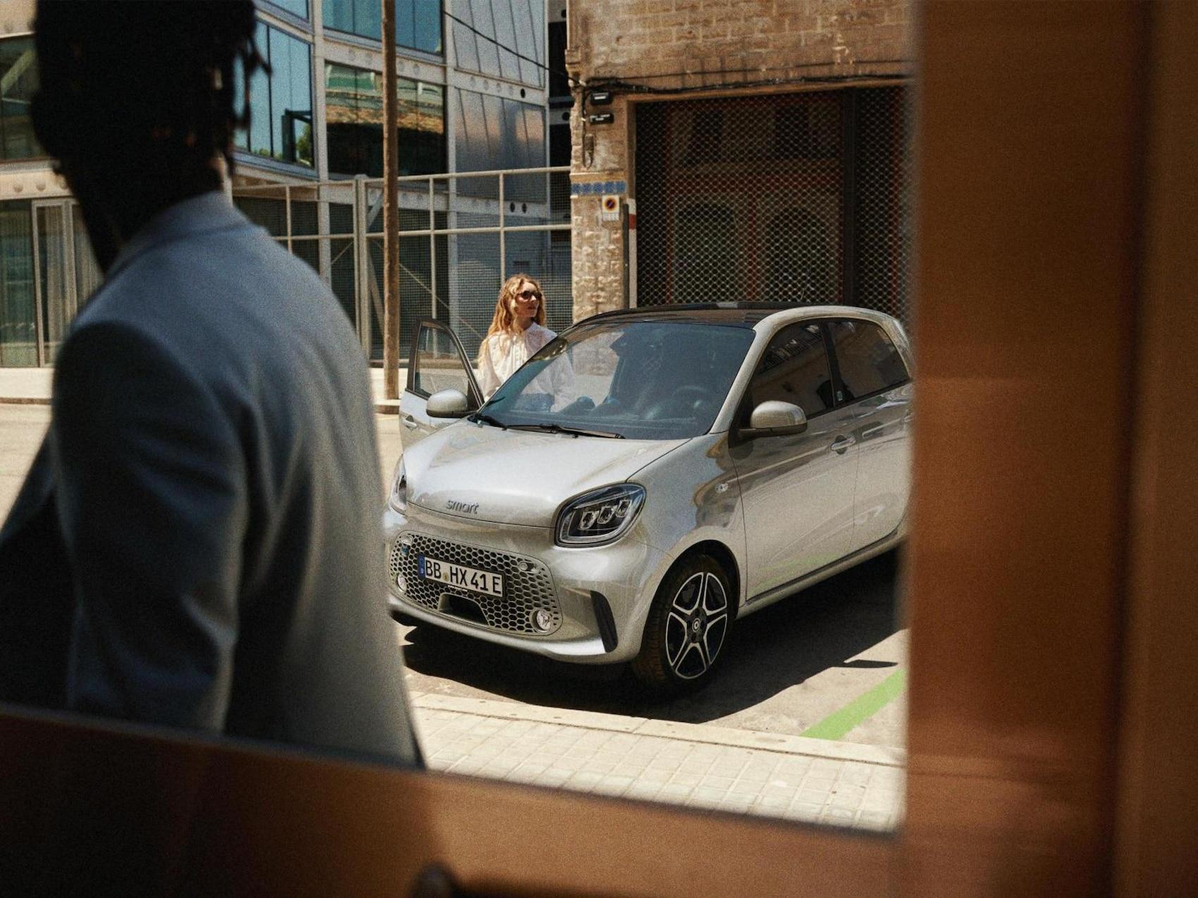 Une femme monte à bord d'une smart EQ forfour, côté passager.