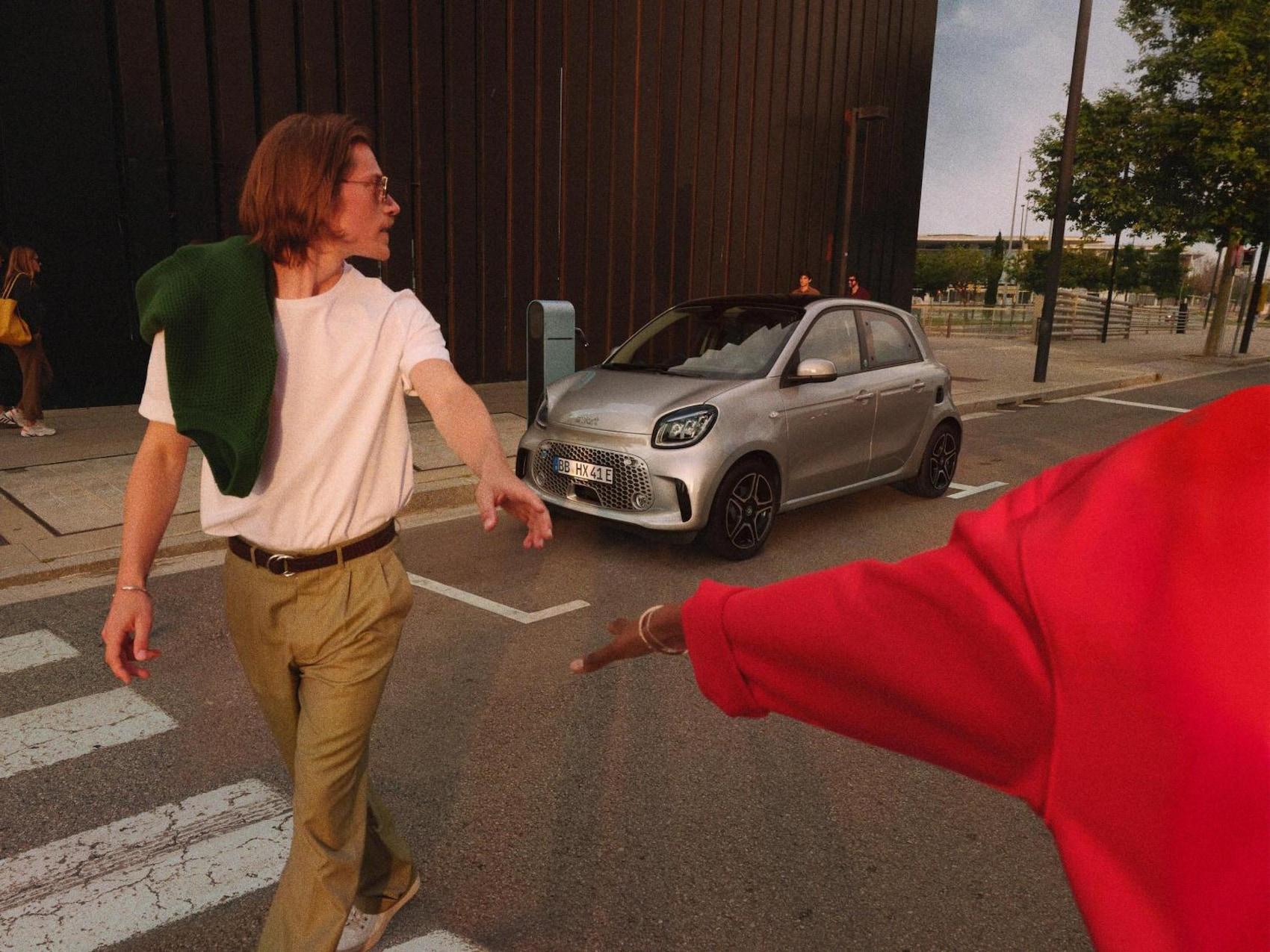 Un homme et une femme traversent un passage piéton avec une smart EQ forfour visible à l'arrière-plan, près d'une borne de recharge.