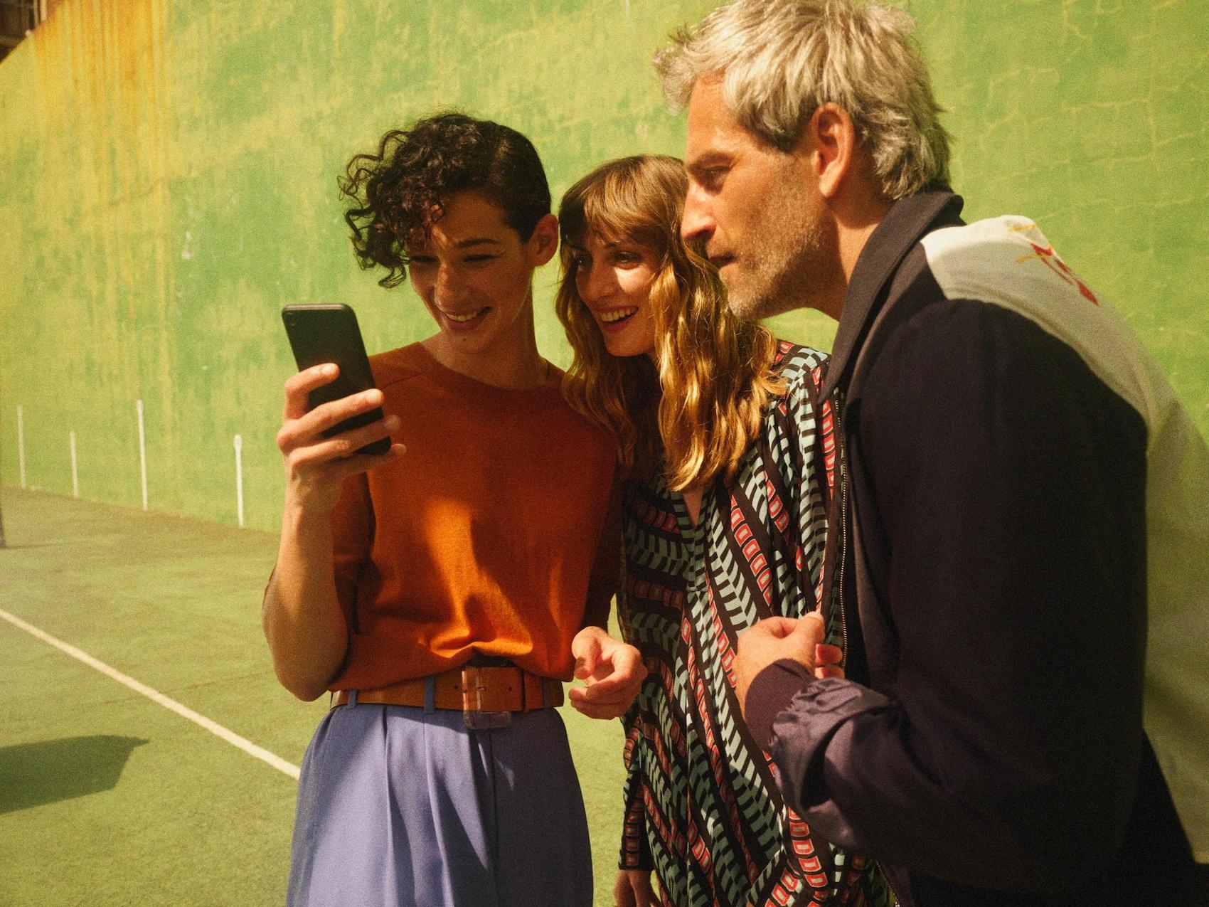 Drei Menschen gucken auf ein Mobiltelefon.