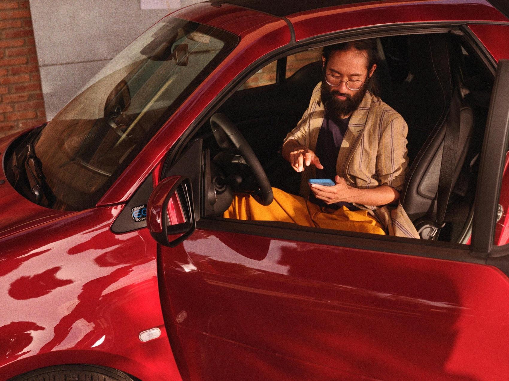 Un homme est assis dans une smart EQ fortwo et regarde son téléphone portable.