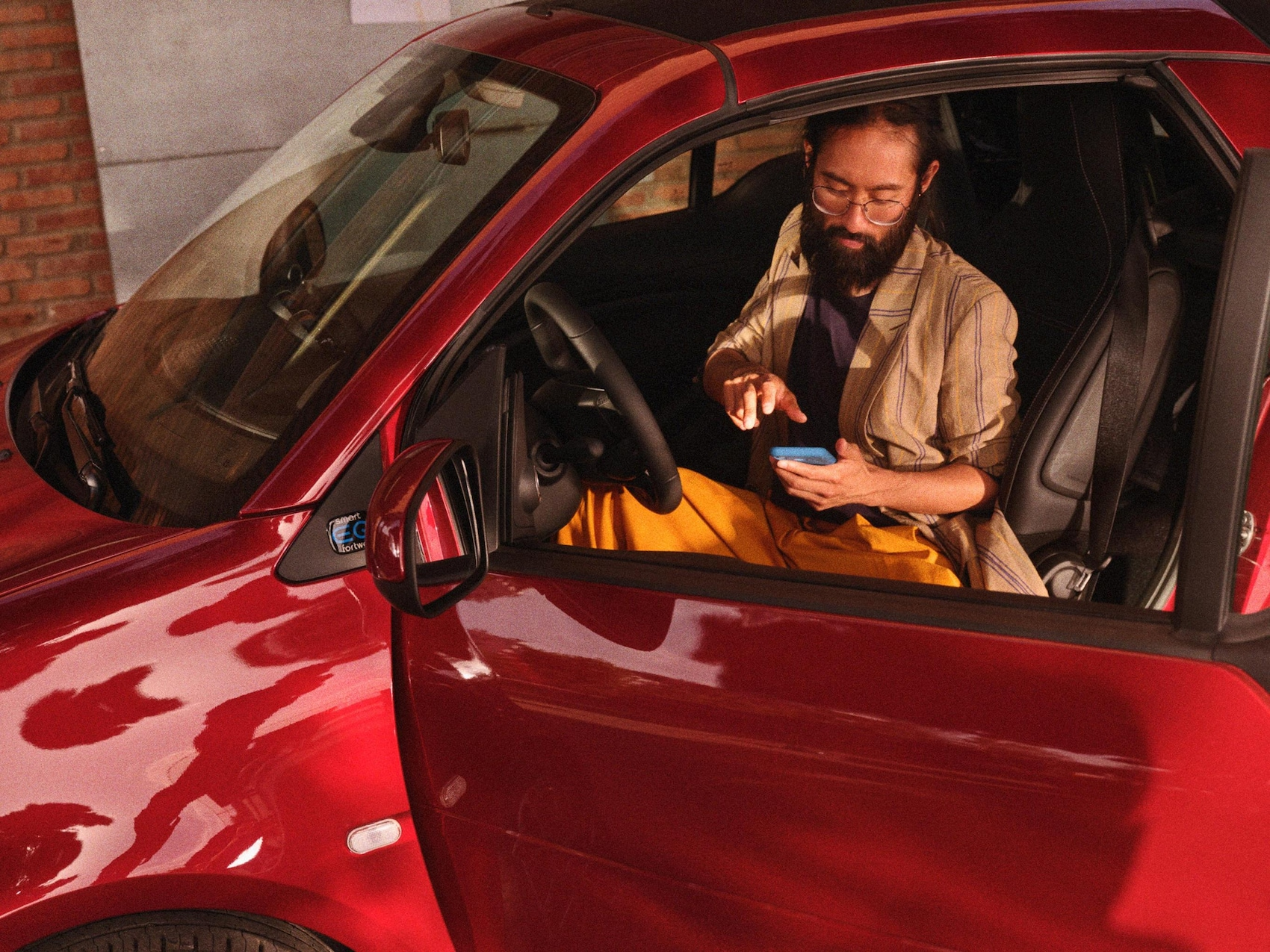 Een man zit in de smart EQ fortwo en kijkt op zijn mobiele telefoon.