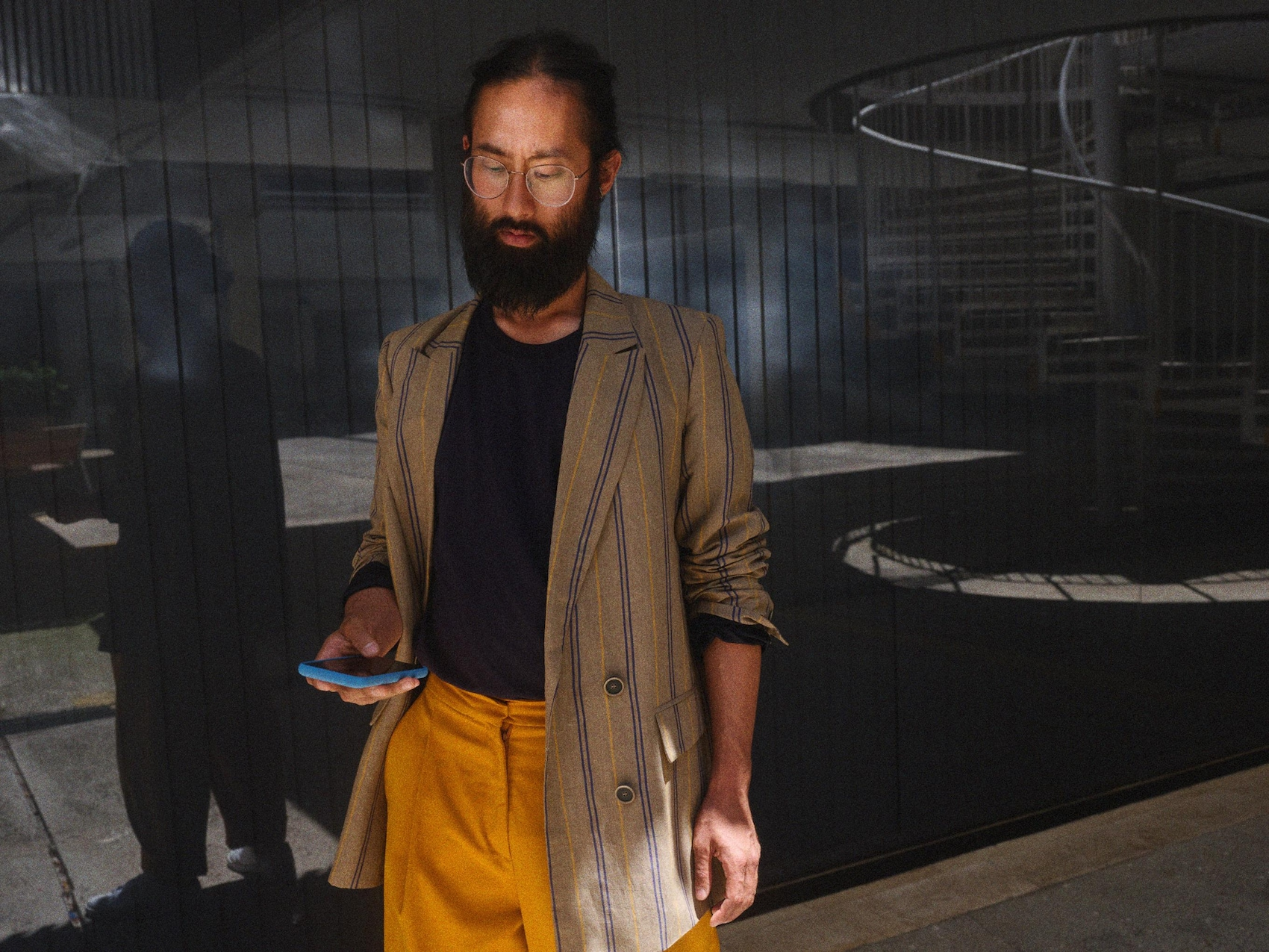 Man met baard kijkt op zijn mobiele telefoon.