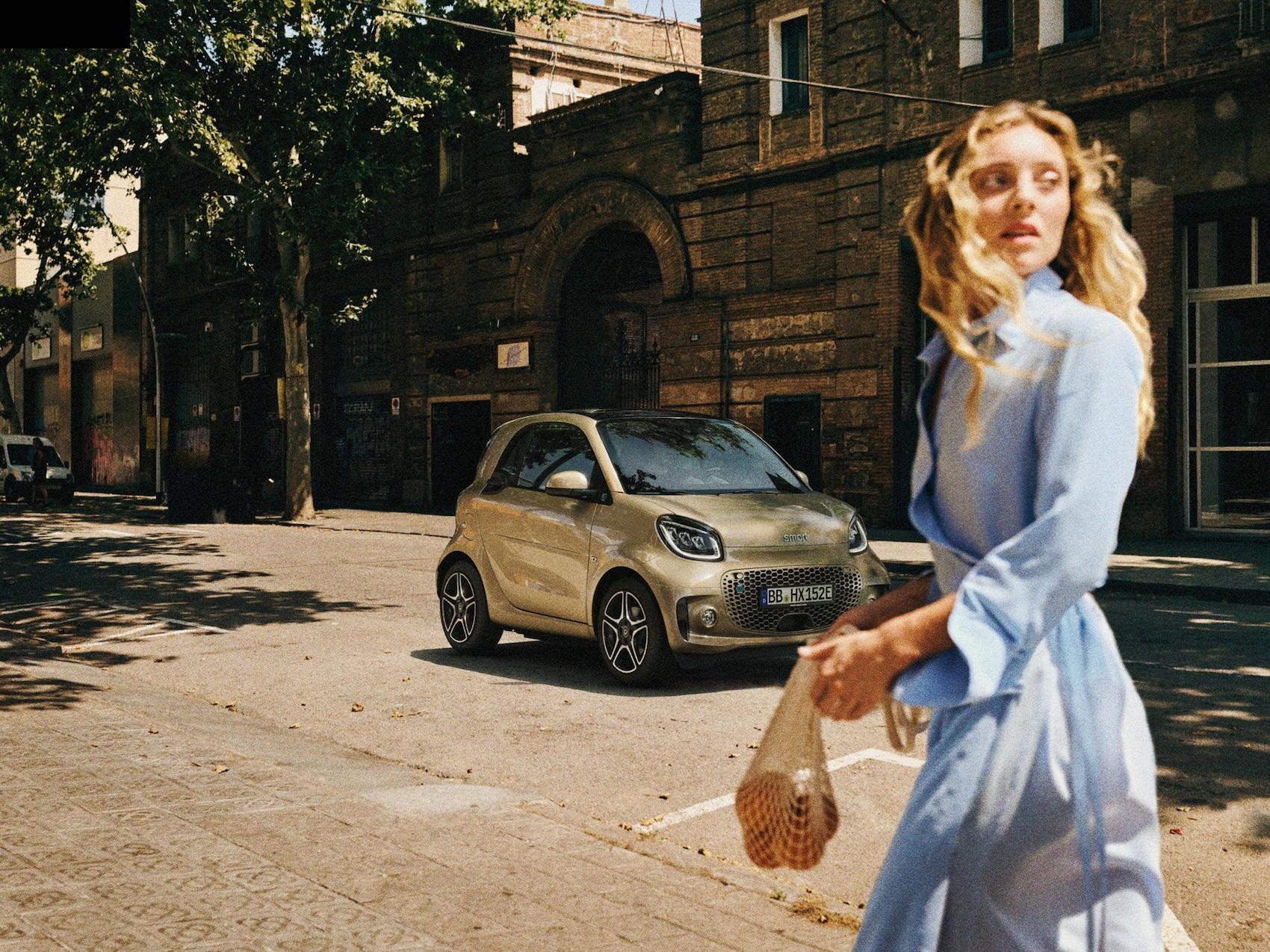 Eine Frau geht an einem auf der Straße fahrenden smart EQ fortwo vorbei