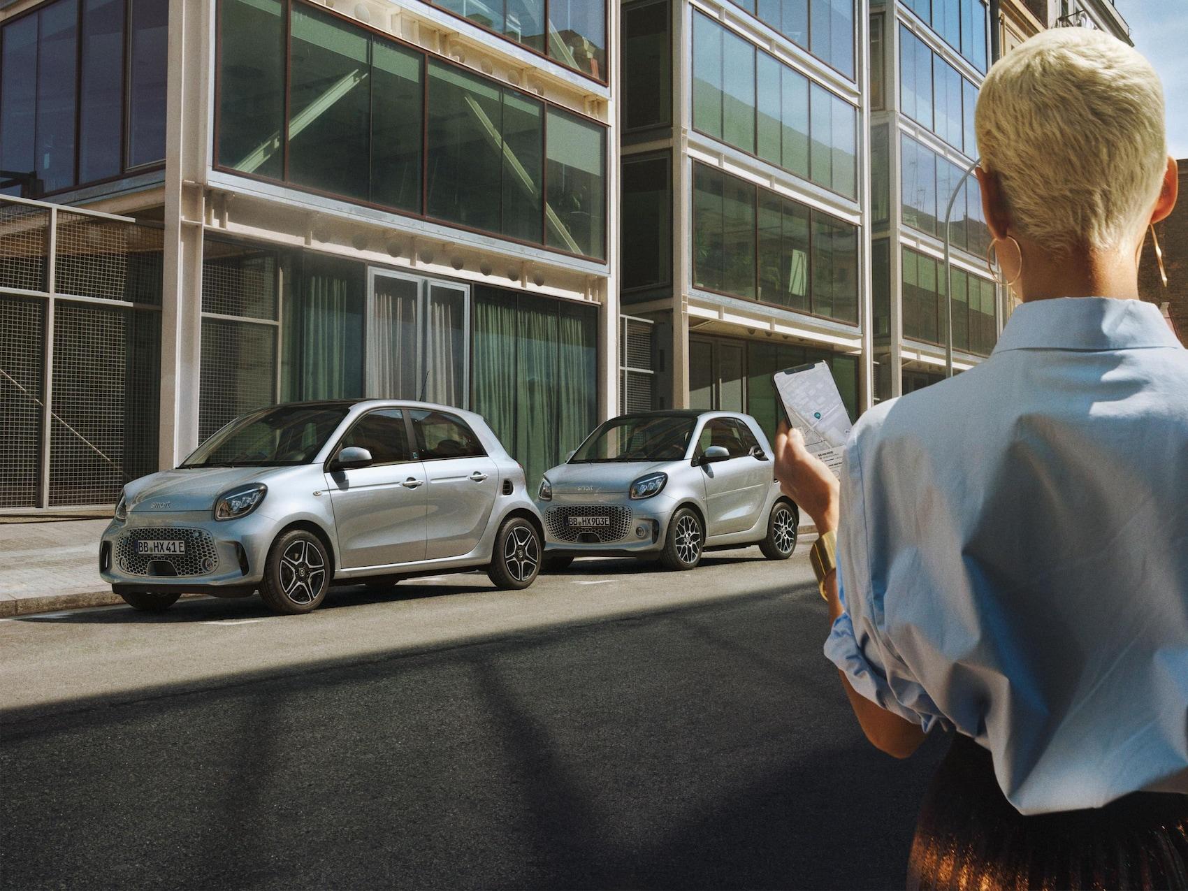Frau mit kurzen blonden Haaren steht mit einem Smartphone vor silbernem smart EQ forfour und smart EQ fortwo.