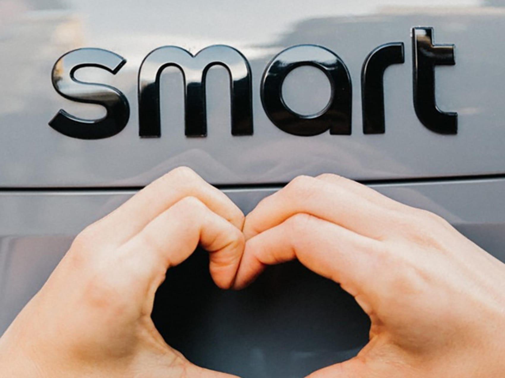 Serce ułożone z rąk na tle szarego logo smart