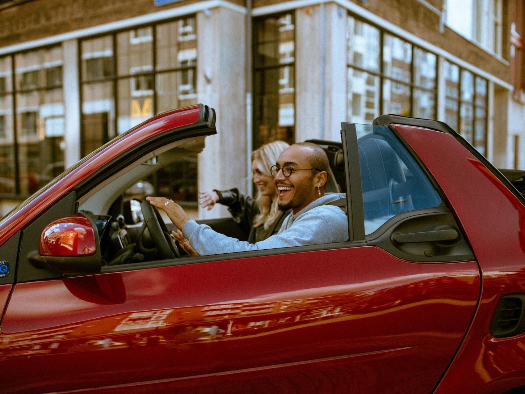 Deux jeunes gens circulent dans une smart EQ fortwo cabrio rouge ouverte.