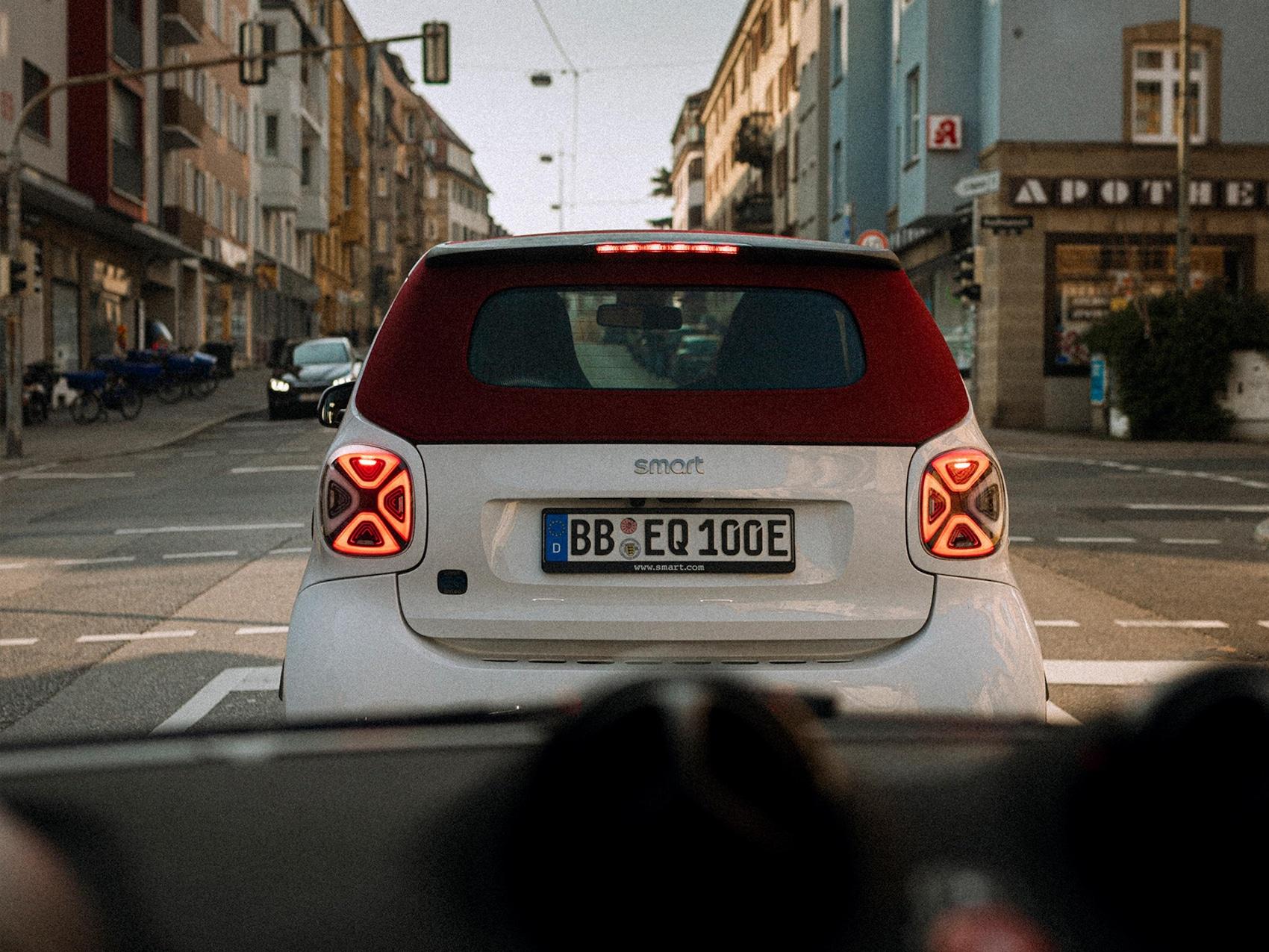 Weißes smart EQ fortwo cabrio mit rotem Dach ist von hinten zu sehen.