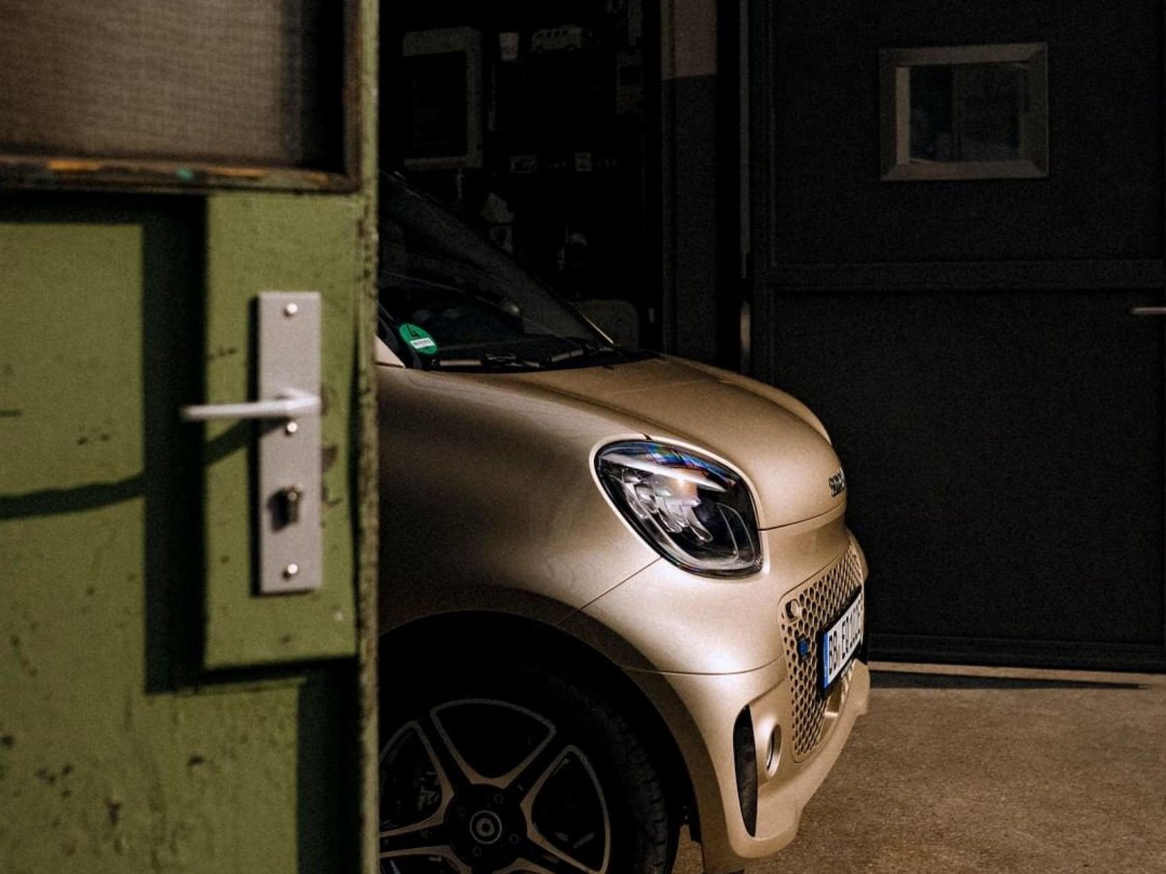 smart EQ fortwo in gold beige steht hinter einer grünen Tür.