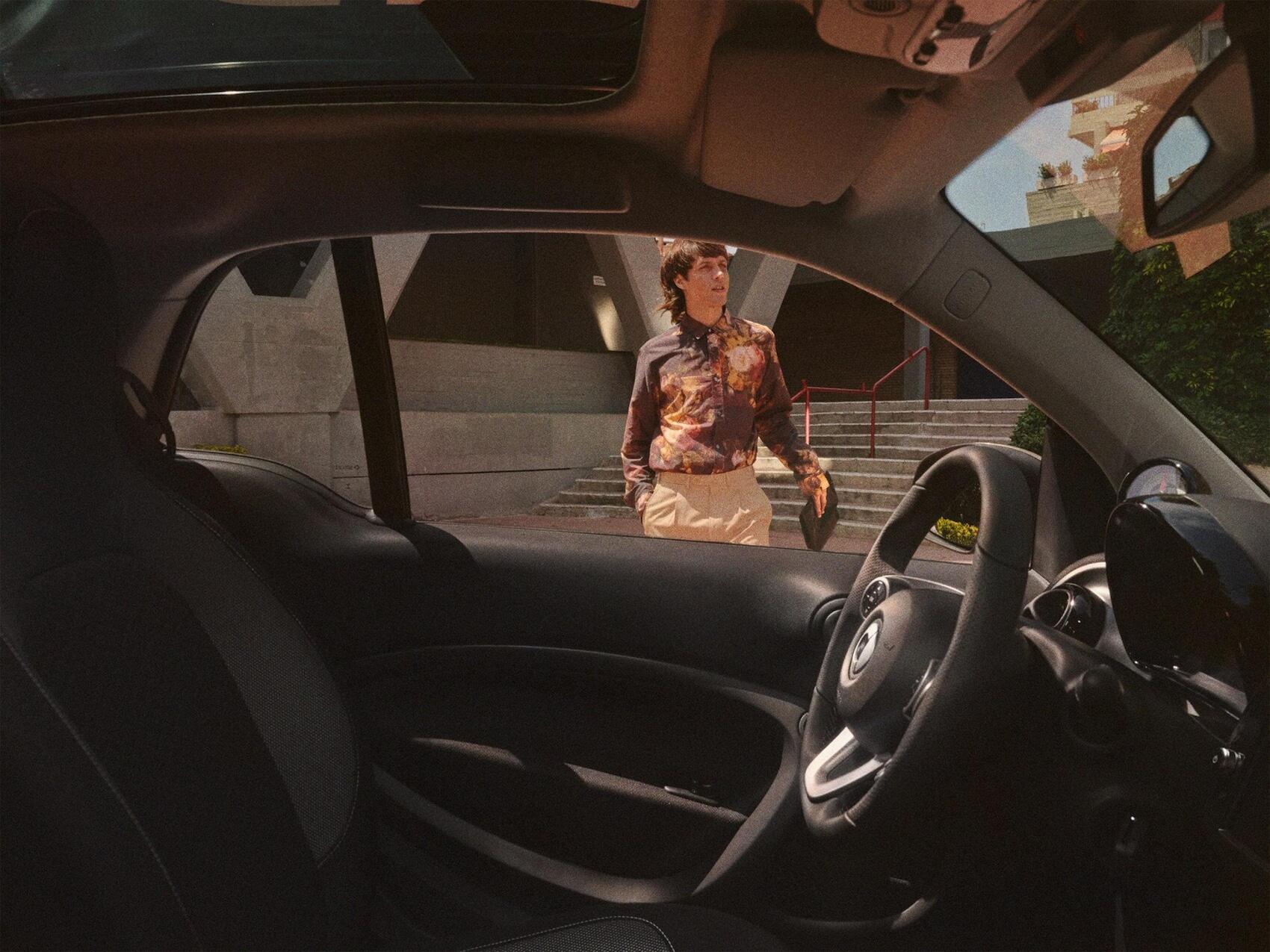 Mann ist durch das Fenster vom Inneren eines smart EQ fortwo zu sehen.