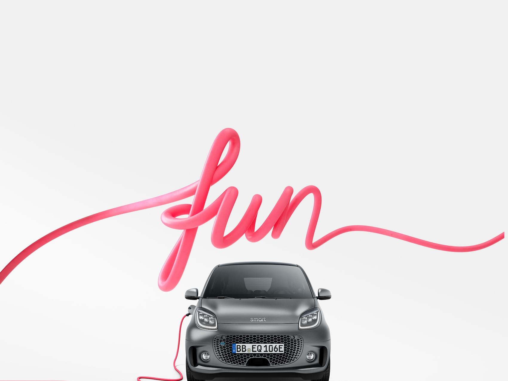 smart EQ fortwo en gris con cable de carga rosa y distintivo «fun»