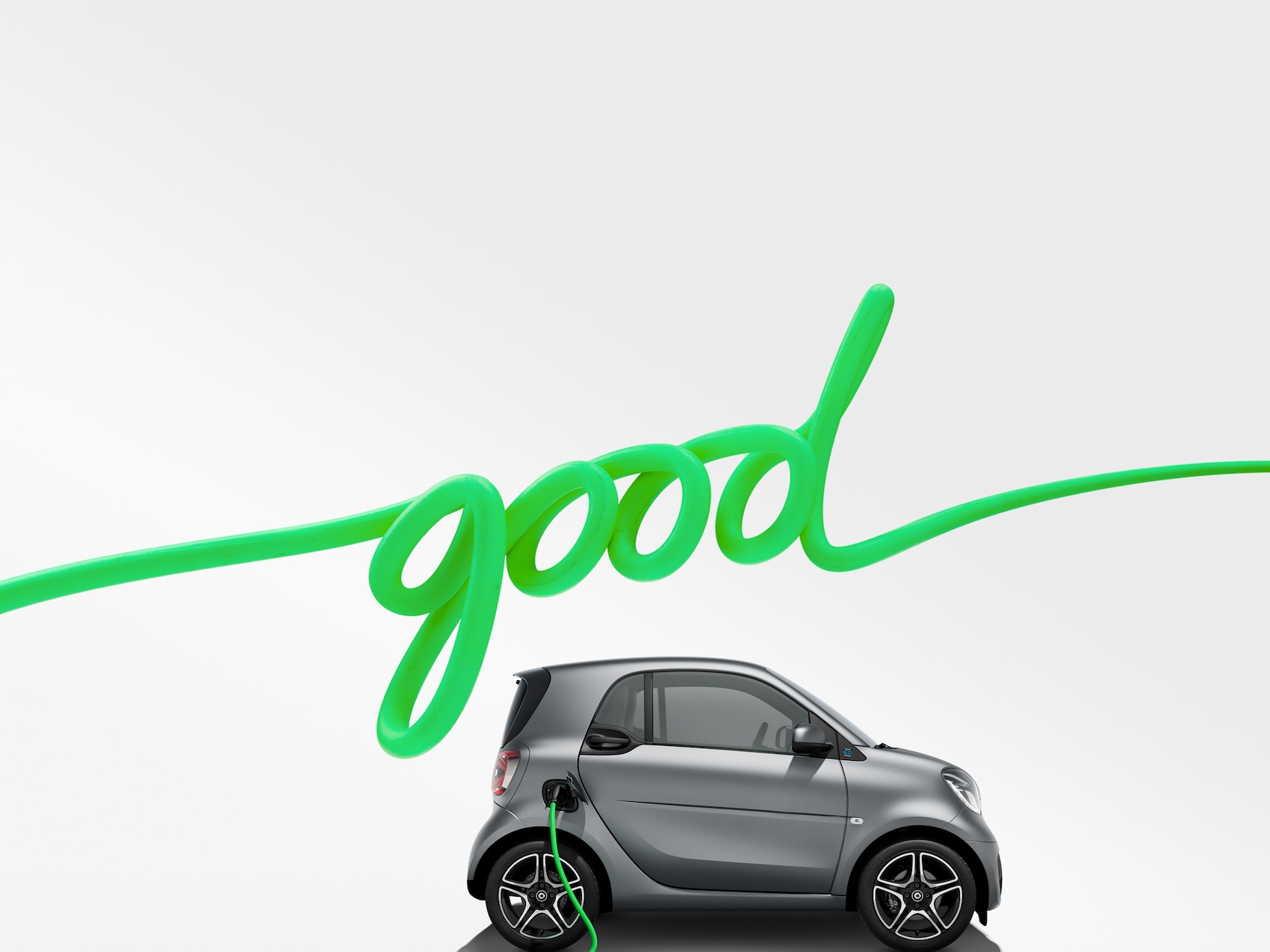 smart EQ fortwo in grau mit grünem Ladekabel und Schriftzug good